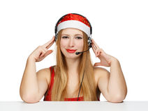 Young woman in santa claus hat and headphones isolated on white. Background Royalty Free Stock Image