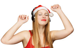 Young woman in santa claus hat and headphones take pleasure from. Music isolated on white background Stock Image