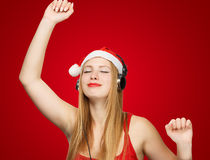 Young woman in santa claus hat and headphones take pleasure from. Music  on red background Stock Images