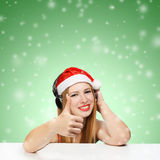 Young woman in santa claus hat and headphones with thumbs up ges. Ture on green background with falling snow Royalty Free Stock Photo