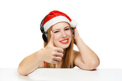Young woman in santa claus hat and headphones with thumbs up ges Royalty Free Stock Photography