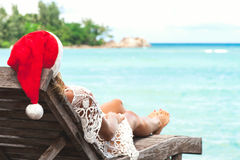 Young woman in santa claus hat sitting in chaise lounge on tropical sea beach Stock Images
