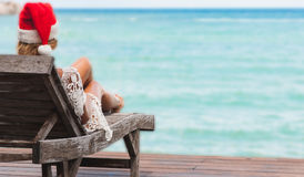 Young woman in santa claus hat sitting in chaise lounge on tropical sea beach Royalty Free Stock Image