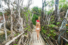 Young Woman in Santa Claus Hat Walk across Authentic Wooden Bridge. Celebrating New Year in hot country royalty free stock image