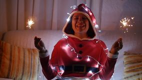 Happy young woman in santa costume with bengal lights. Young woman in santa costume with bengal lights stock video