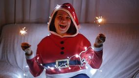 Happy young woman in santa costume with bengal lights. Young woman in santa costume with bengal lights stock video footage