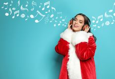 Young woman in Santa costume listening to Christmas music. On color background royalty free stock image