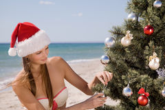 Young woman in Santa hat on beach decorates a Christmas tree balls Stock Images