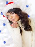 Young woman in a Santa Hat blowing a kiss Stock Photos