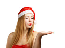 Young woman in santa hat blows on open hand Royalty Free Stock Image