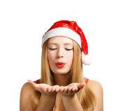 Young woman in santa hat blows on open hands Royalty Free Stock Images