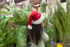 Young woman in santa hat choosing Christmas tree Stock Photos