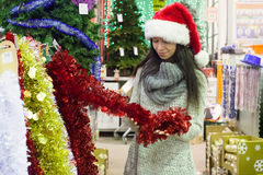 Young woman in santa hat choosing decorations on Stock Images