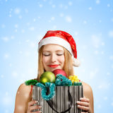 Young woman in santa hat with christmas attributes and gifts Royalty Free Stock Photo