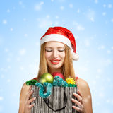 Young woman in santa hat with christmas attributes and gifts Royalty Free Stock Photos
