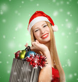 Young woman in santa hat with christmas attributes and gifts. Beautiful young woman in santa claus suit holding box with christmas and new year attributes and Royalty Free Stock Photo