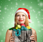 Young woman in santa hat with christmas attributes and gifts. Beautiful young woman in santa claus suit holding box with christmas and new year attributes and Royalty Free Stock Photos