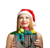 Young woman in santa hat with christmas attributes and gifts. Beautiful young woman in santa claus suit holding box with christmas and new year attributes and Royalty Free Stock Image
