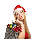 Young woman in santa hat with christmas attributes and gifts. Beautiful young woman in santa claus suit holding box with christmas and new year attributes and Stock Photos