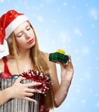 Young woman in santa hat with christmas attributes and little gi. Beautiful young woman in santa claus suit holding box with christmas and new year attributes Royalty Free Stock Photos