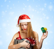 Young woman in santa hat with christmas attributes and little gi Stock Photos