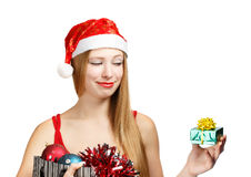 Young woman in santa hat with christmas attributes and little gi. Beautiful young woman in santa claus suit holding box with christmas and new year attributes Stock Photography