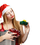 Young woman in santa hat with christmas attributes and little gi. Beautiful young woman in santa claus suit holding box with christmas and new year attributes Stock Images