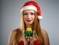 Young woman in santa hat with christmas gift box Royalty Free Stock Image
