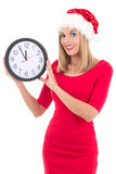 Young woman in santa hat with clock posing isolated on white Royalty Free Stock Images