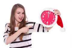 Young woman in santa hat with clock posing Royalty Free Stock Photos