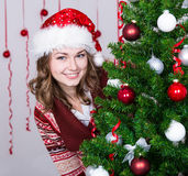 Young woman in santa hat with decorated Christmas tree Stock Photo