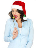 Young Woman in Santa Hat Eating a Brussel Sprout off a Fork Stock Image