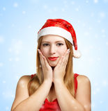 Young woman in santa hat with expressive gesture. Beautiful young woman in santa claus hat with expressive gesture on blue background with falling snowflakes Stock Photo