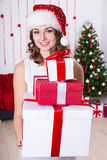 Young woman in santa hat with heap of presents near Christmas tr Stock Image
