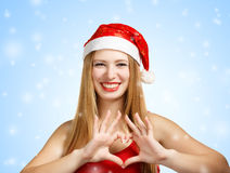 Young woman in santa hat with heart shape. Beautiful young woman in santa claus hat heart shape on blue background with falling snowflakes Royalty Free Stock Images