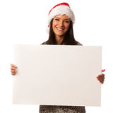 Young woman in santa hat holding blank board for advertisement. Stock Photography