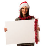 Young woman in santa hat holding blank board for advertisement. Stock Photos