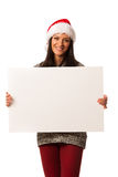 Young woman in santa hat holding blank board for advertisement. Stock Image