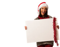 Young woman in santa hat holding blank board for advertisement. Royalty Free Stock Photography