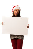 Young woman in santa hat holding blank board for advertisement. Royalty Free Stock Image