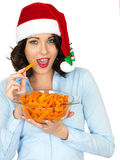 Young Woman in Santa Hat Holding a Bowl of Carrots Stock Photography