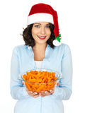 Young Woman in Santa Hat Holding a Bowl of Carrots Royalty Free Stock Images