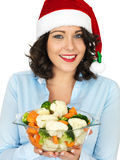 Young Woman in Santa Hat Holding Bowl of Cooked Mixed Vegetables. A DSLR royalty free image, young happy festive woman smiling, with dark hair, holding a glass royalty free stock photo