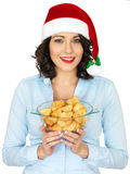 Young Woman in Santa Hat Holding Bowl or Cooked Roast Potatoes Royalty Free Stock Photo