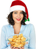 Young Woman in Santa Hat Holding Bowl or Cooked Roast Potatoes Stock Photo