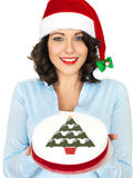 Young Woman in Santa Hat Holding a Christmas Fruit Cake Royalty Free Stock Photo