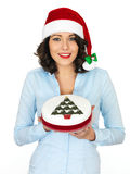 Young Woman in Santa Hat Holding a Christmas Fruit Cake Royalty Free Stock Image
