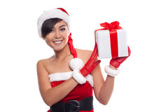 Young woman with Santa hat holding Christmas gift against white Stock Photos