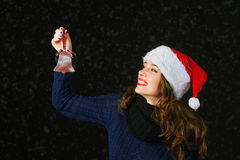 Young woman in Santa hat holding Christmas toys . Christmas time Stock Photography