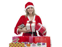 Young woman with Santa hat holding gift boxes and shopping bags Stock Photos